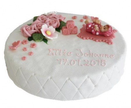 Hvit marsipankake med rosa roser som pynt, påskrift og en babyfigur