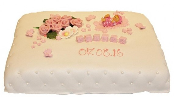 Marsipankake med rosa roser, perler og en babyfigur som pynt