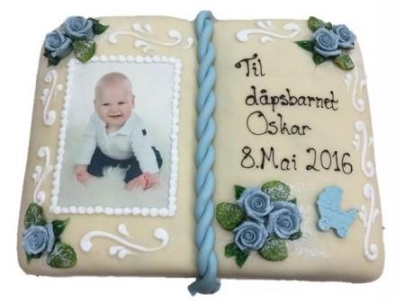 Marsipankake formet som en bok med bilde av en baby, påskrift og blå roser som pynt