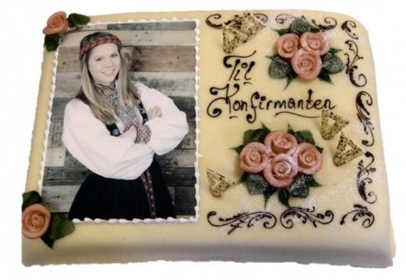 """Marsipankake med bilde av en jente i bunad, påskriften """"Til Konfirmanten"""" og rosa roser som pynt"""
