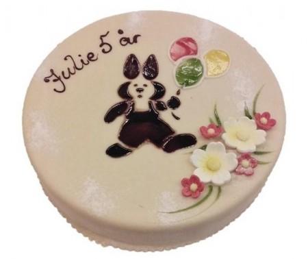 Marsipankake med skrift pyntet med blomster og en tegnet kanin med ballonger