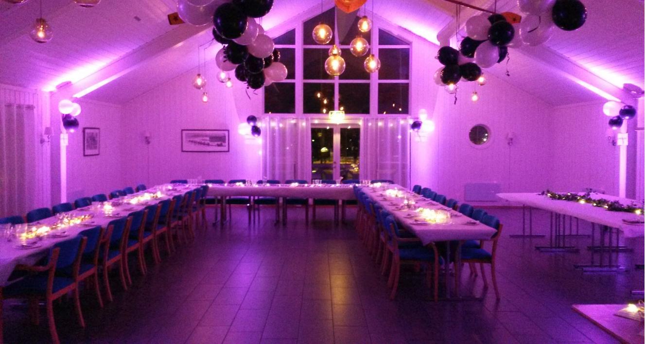 Lilla opplyst selskapslokale med svarte og hvite ballonger i taket og bord dekket til middag