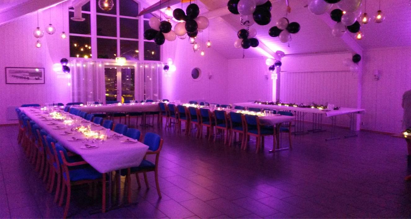 Lilla opplyst selskapslokale med ballonger i taket og bord dekket til middag
