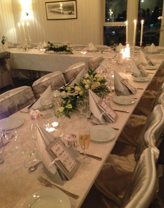 Bilde av et bord dekket til en flott middag levende lys og blomster