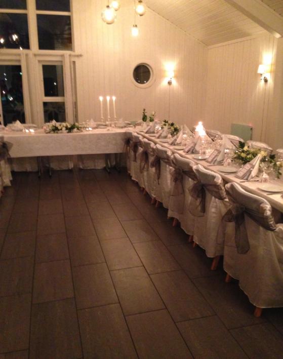 Bilde av et selskapslokale med hvite vegger med bord dekket til en flott middag