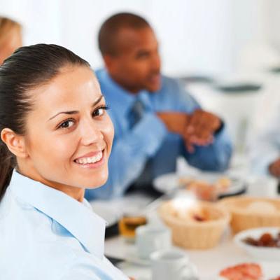 Dame med brunt år som smiler til kameraet med et bord og andre mennesker i bakgrunnen
