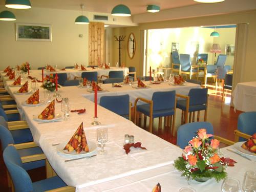 Bilde av et selskapslokale med bord med hvite duker dekket til middag og blå stoler
