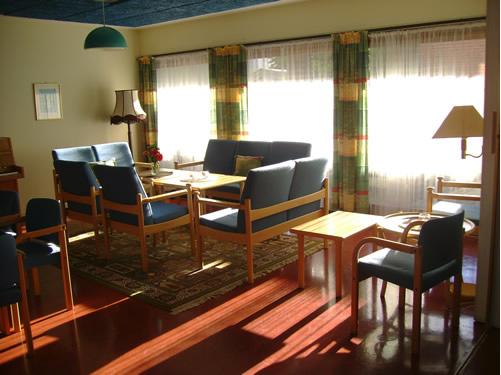 Bilde av en stue møblert med sofaer og stoler med blå puter samt noen trebord