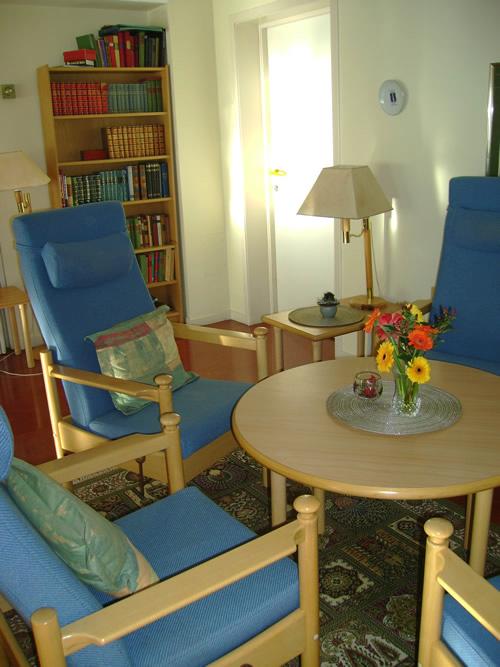 Bilde av en stue med blå lenestoler som står rundt et rundt trebord med en bokhylle i bakgrunnen